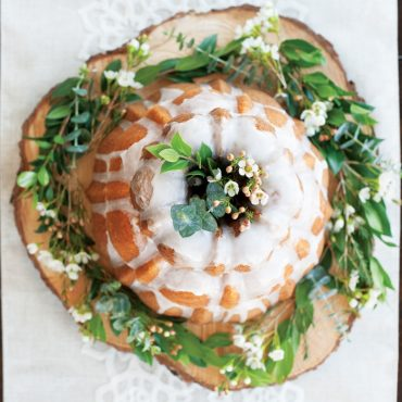 Overhead 3 tiered baked cakes with glaze, flowers around base of cake and in middle of cake
