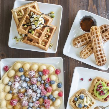 Variety of waffle shapes plated, variety of toppings