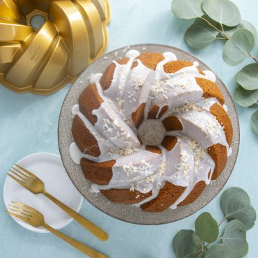 75th Anniversary Braided Bundt® Baked Cake with glaze, pan and plate on background